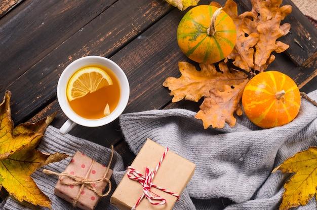 Tasse tee mit zitrone auf dunklem holztisch mit herbstlaub, kürbisse. herbstdekor, herbststimmung, herbststillleben. konzept der herbstsaison. thanksgiving und halloween-feiertag. flach legen, platz kopieren