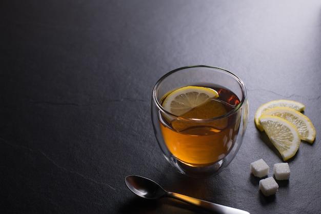Tasse tee mit zitrone auf schwarzem granithintergrund