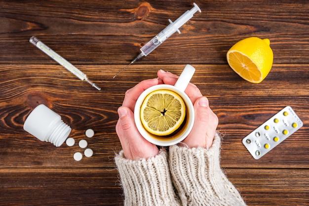 Tasse tee mit zitrone in weiblichen händen. zitrone, thermometer und pillen auf holzoberfläche. kältebehandlung. grippe-saison.