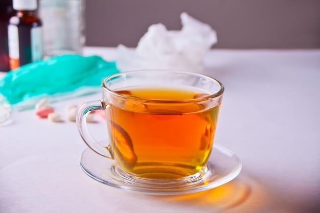 Tasse tee mit zitrone, thermometer, medikamenten und pillen auf weißer tabelle. krankheitskonzept.