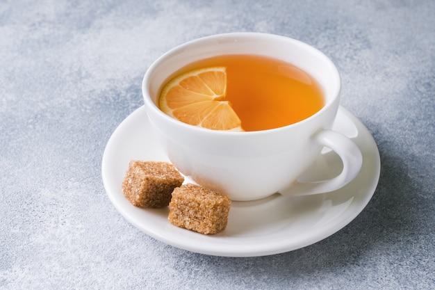 Tasse tee mit zitrone und braunem zucker auf dem tisch.