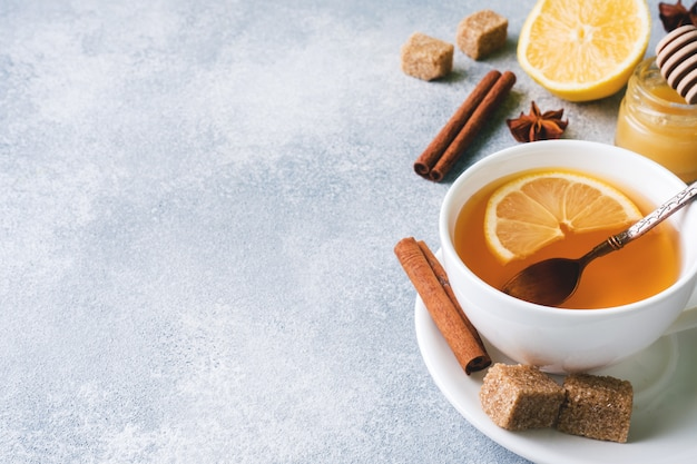 Tasse tee mit zitrone und braunem zucker, zimt und anis auf dem tisch.