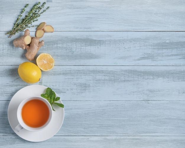 Tasse tee mit zitrone und minze auf hölzernem blauem hintergrund. draufsicht und kopierraum