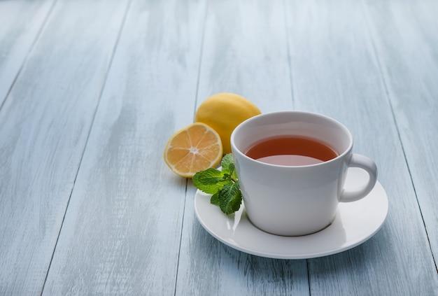 Tasse tee mit zitrone und minze auf hölzernem blauem hintergrund. schließen und speicherplatz kopieren