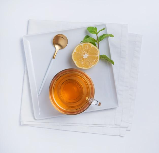 Tasse tee mit zitrone und minze auf quadratischem teller weißem hintergrund. draufsicht