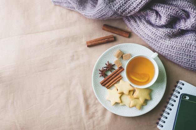 Tasse tee mit zitrone und plätzchen, honig und zimtstangen, sternanis auf der decke