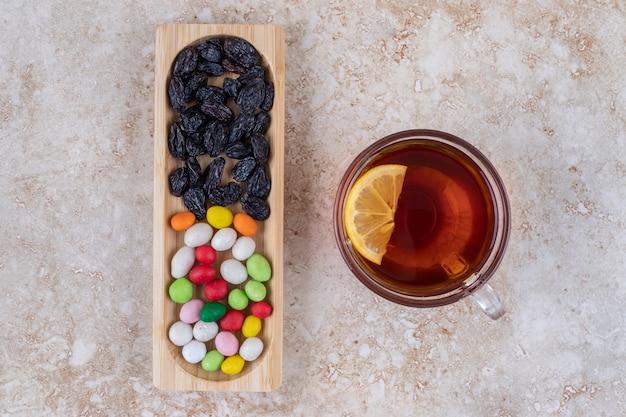 Tasse tee mit zitrone und teller mit süßigkeiten auf marmoroberfläche