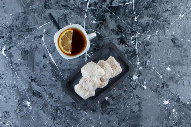 Tasse tee mit zitrone und teller mit zuckerwatte auf marmoroberfläche.