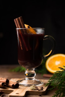 Tasse tee mit zitrone und zimt auf holzbrett