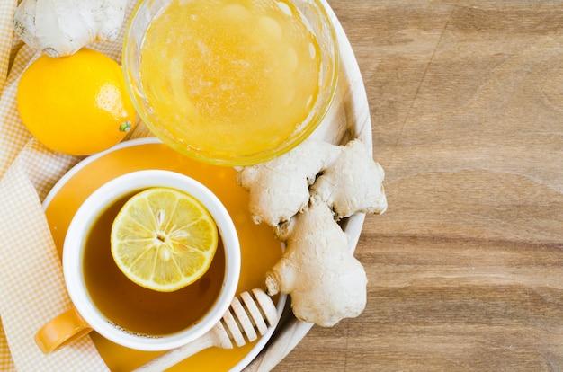 Tasse tee mit zitroneningwer und -honig.