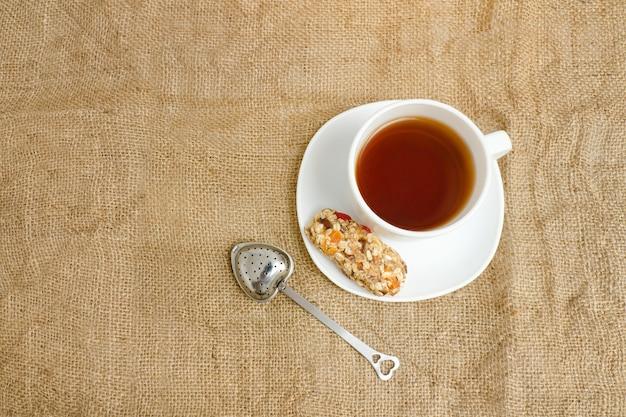 Tasse tee, müsliriegel und teesieb auf sackleinen. ansicht von oben