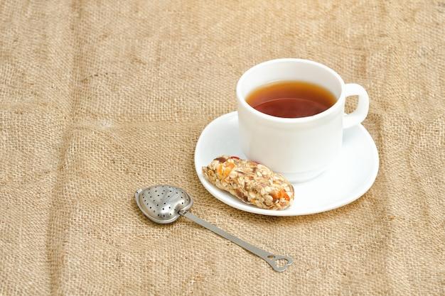 Tasse tee, müsliriegel und teesieb auf sackleinen