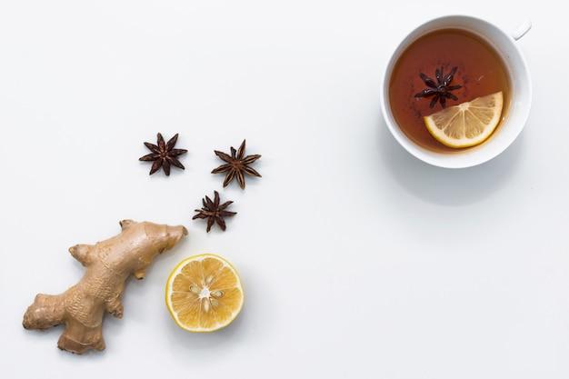 Tasse tee nahe ingwer- und zitronenhälfte