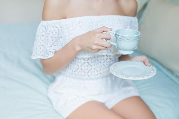 Tasse tee oder kaffee in weiblichen händen hautnah am morgen