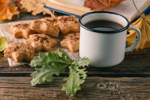 Tasse tee oder kaffee mit herbstlaub und keksen. saisonal, teezeit, stilllebenkonzept.