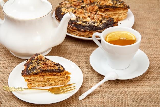 Tasse tee, porzellan-teekanne und hausgemachter schokoladen-puff-kuchen auf dem tisch mit sackleinen