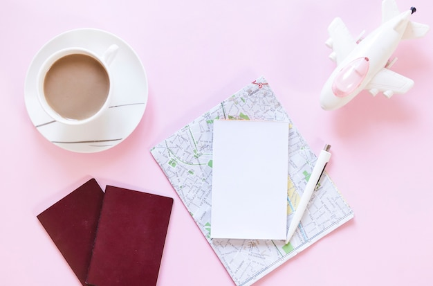 Tasse tee; reisepass; karte; papier; stift und flugzeug auf rosa hintergrund