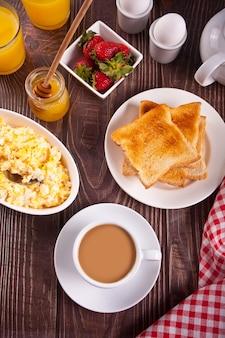 Tasse tee, rührei, gekochte eier und knuspriger toast