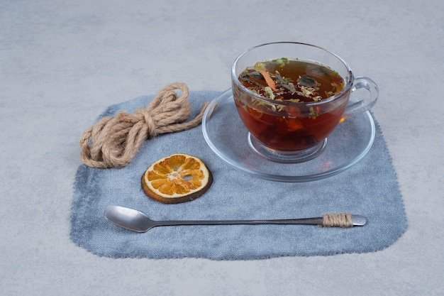 Tasse tee, seil und getrocknete orangenscheibe auf tischdecke.