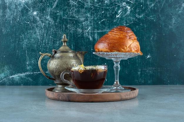 Tasse tee, teetasse und gebäck auf holzplatte.