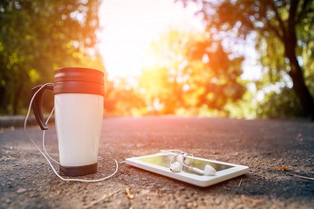 Tasse tee, telefon und kopfhörer liegen auf der straße