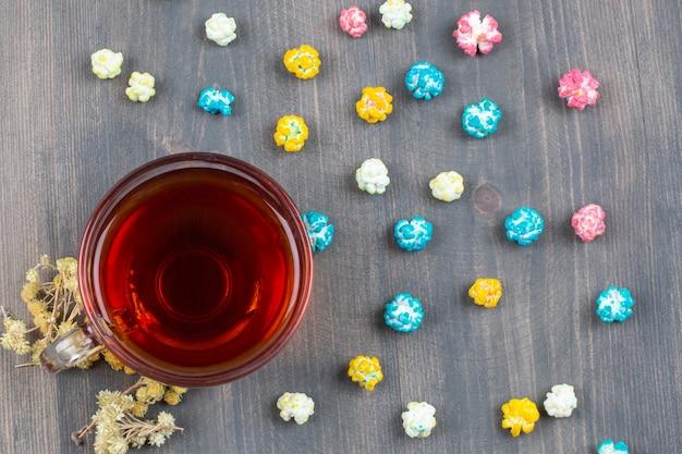 Tasse tee, trockenblumen und buntes popcorn auf holzoberfläche