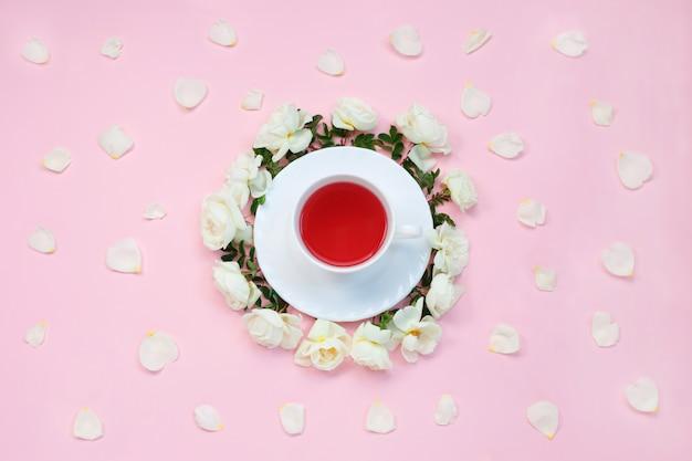 Tasse tee, umgeben von weißen rose