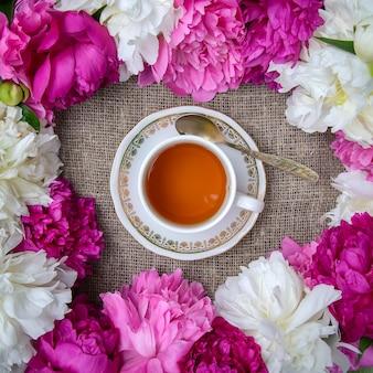 Tasse tee umgeben von weißen und rosa pfingstrosenblumen auf einem leinwandhintergrund