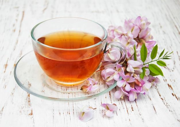 Tasse tee und akazienblumen