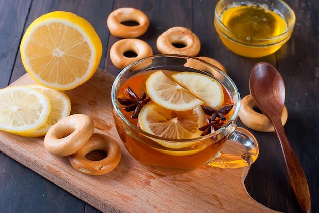 Tasse tee und bagel auf einem holztisch.