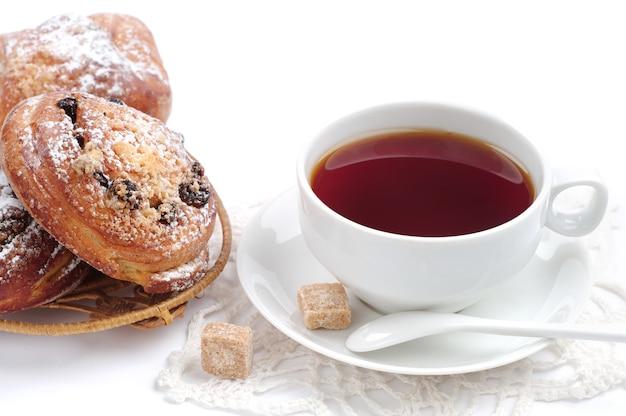 Tasse tee und brötchen mit rosinen auf weißem hintergrund