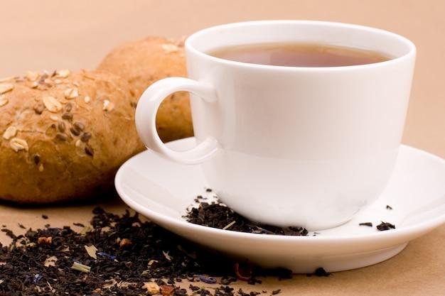 Tasse tee und brotnahaufnahme auf braunem hintergrund
