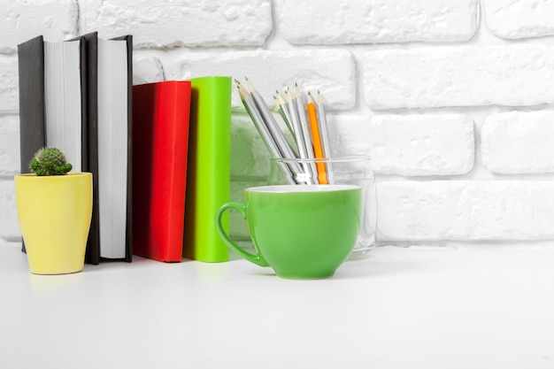 Tasse tee und bücher auf dem tisch