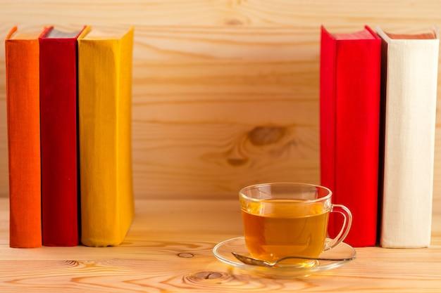 Tasse tee und bücher auf hölzernem hintergrund