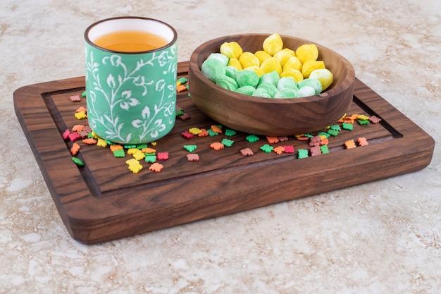 Tasse tee und bunte bonbons auf holzbrett