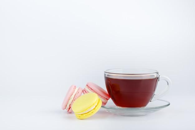 Tasse tee und bunte makronen auf weißem hintergrund
