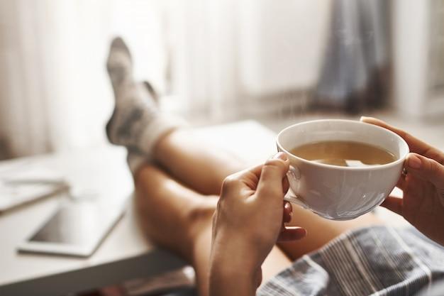 Tasse tee und chill. frau, die auf couch liegt, beine auf kaffeetisch hält, heißen kaffee trinkt und morgen genießt, in verträumter und entspannter stimmung ist. mädchen im übergroßen hemd macht pause zu hause