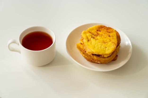 Tasse tee und croutons brot und ei in teller auf weißem tisch. schnelles und einfaches frühstück.