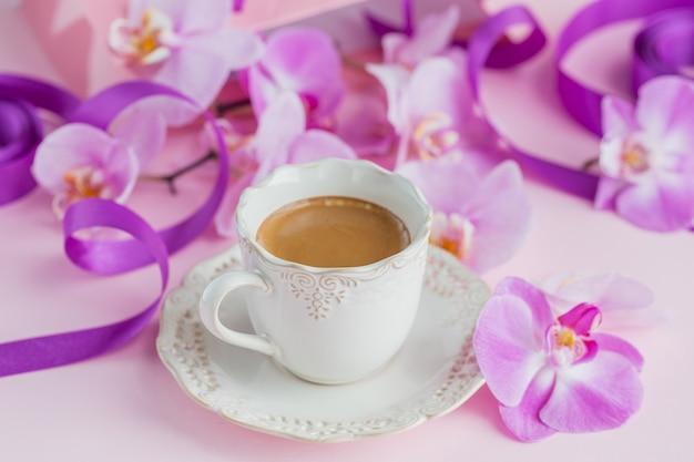 Tasse tee und fliegende orchideenblumen auf hellrosa