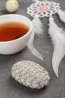 Tasse tee und gehäkelter kiesel