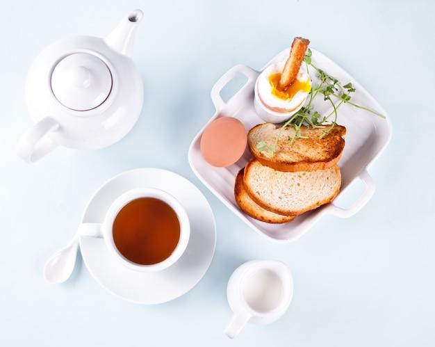 Tasse tee und gekochtes ei in eierbecher auf holzbrett mit knusprigem toast.