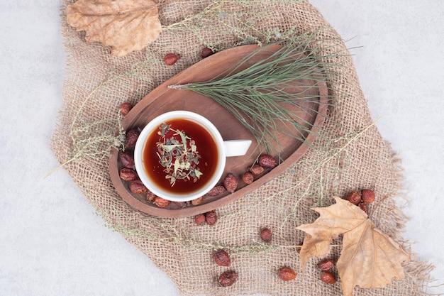 Tasse tee und getrocknete preiselbeeren auf sackleinen. hochwertiges foto