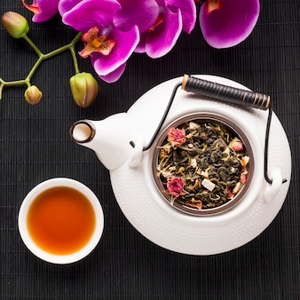 Tasse tee und getrocknetes kraut mit orchideenblume auf schwarzem tischset