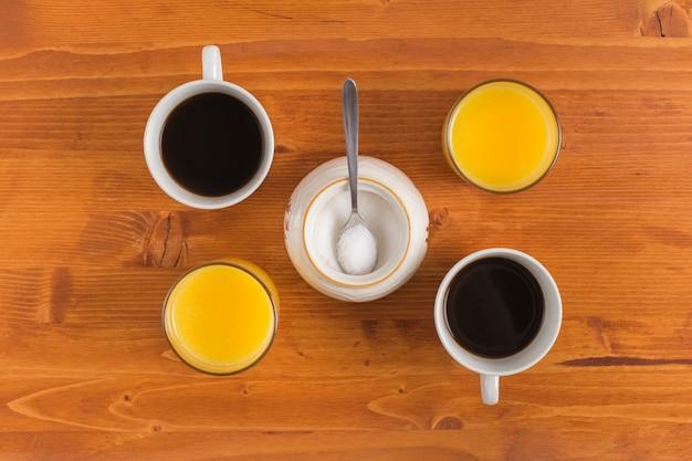 Tasse tee und glas saft auf hölzernem schreibtisch