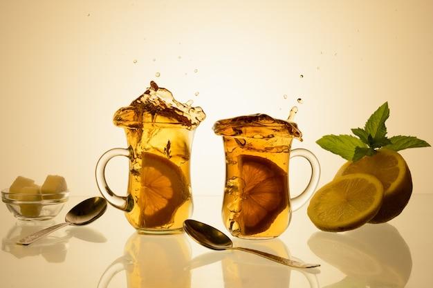 Tasse tee und glasteekanne auf glas mit orangefarbenem hintergrund.