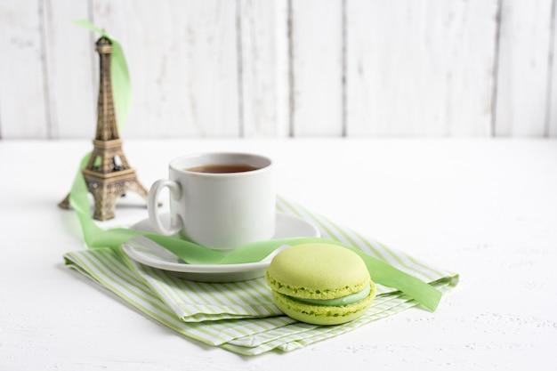 Tasse tee und grüne französische makronen auf einem weißen hölzernen