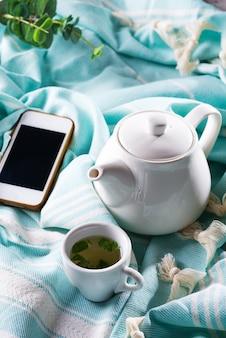Tasse tee und handy in einem bett mit einer teekanne auf einem blauen plaid