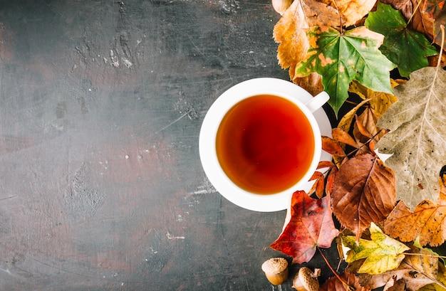 Tasse tee und haufen von blättern