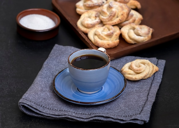 Tasse tee und hausgemachte quark-shortbread-plätzchen formen rose. dunkler hintergrund.