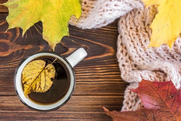 Tasse tee und herbstahornblätter